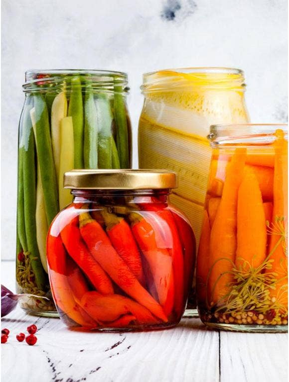 A front view of jars filled with different kinds of pickled vegetables.